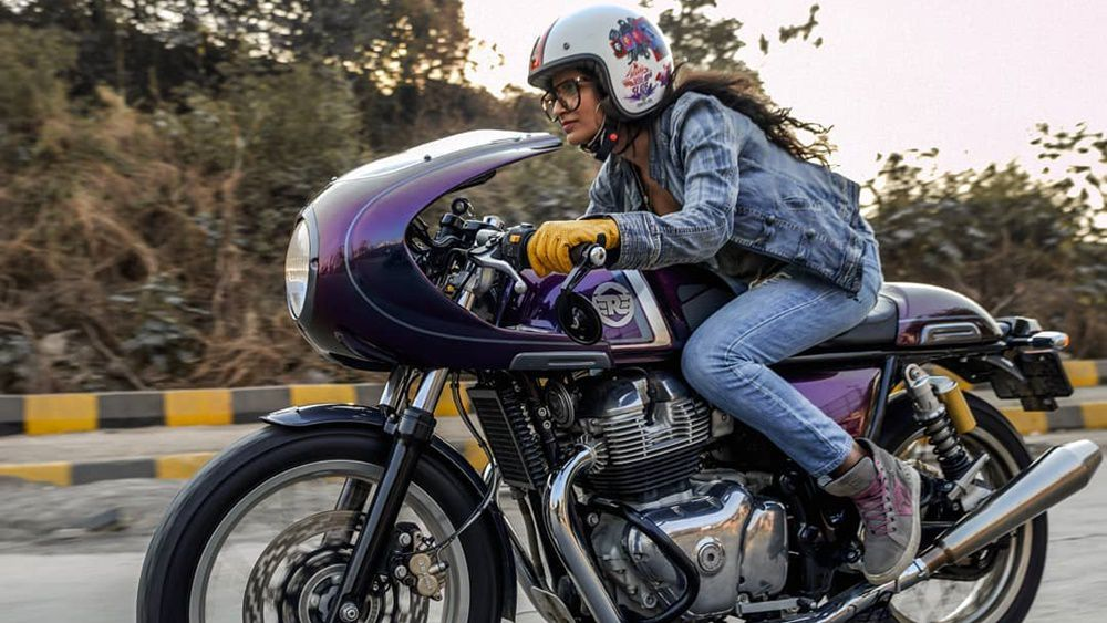 girl rides cafe racer motorcycle with helmet