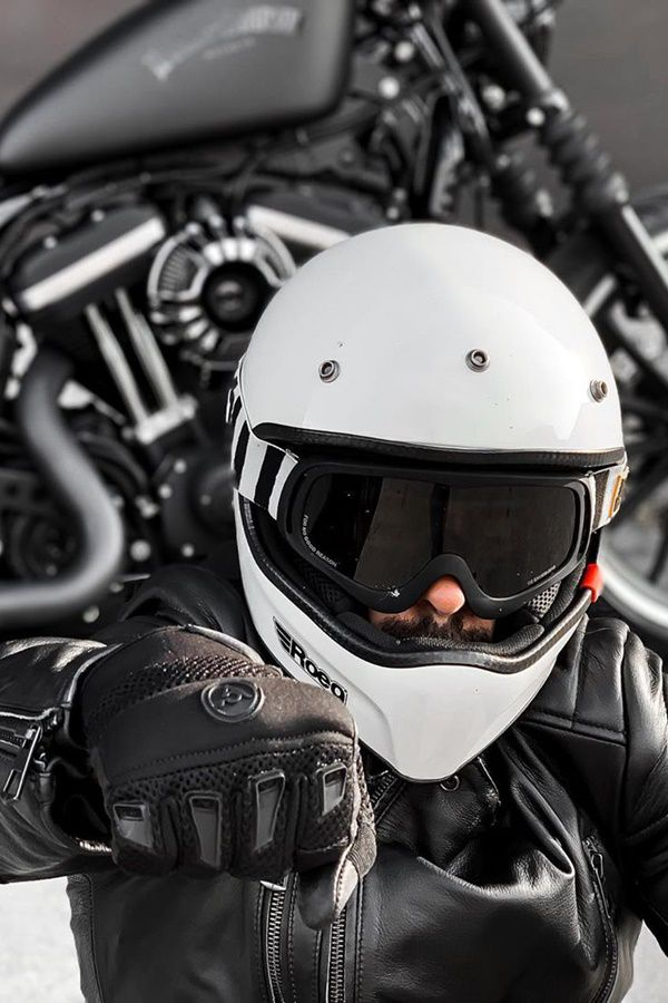 Motorcycle rider with white helmet fist bumps