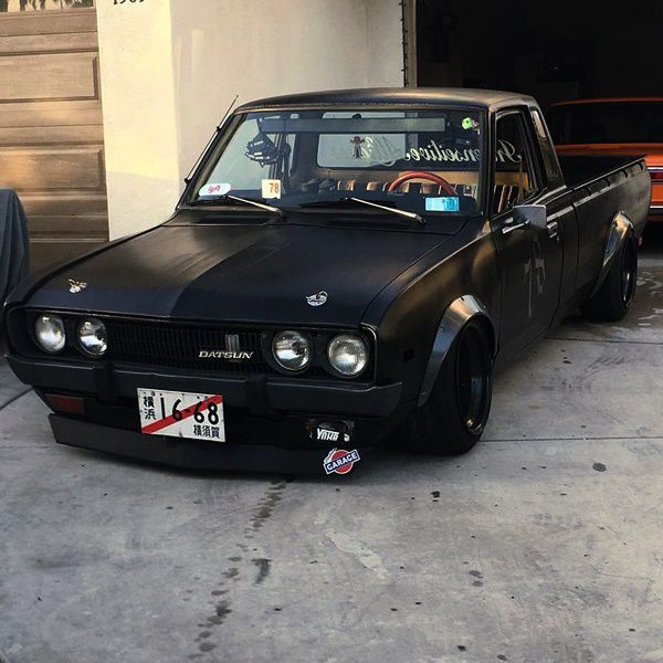 datsun 620 black truck infront of garage