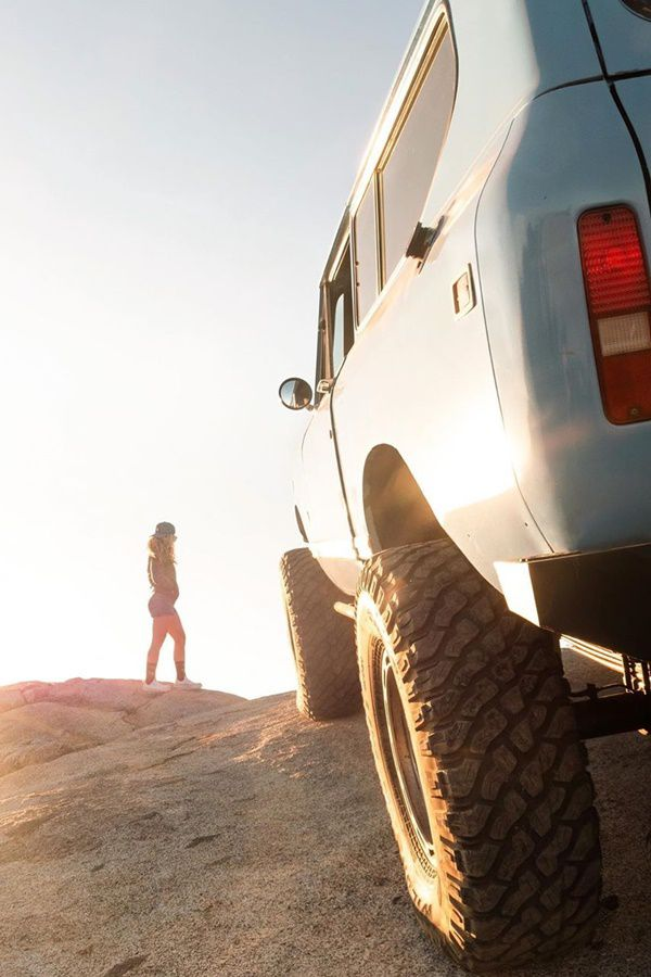 girl and suv on rock